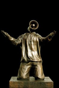 Ohm boy - a sculpture by Hugo Farmer. A person wearing a hoody in on their knees with their hands outstretched. Their head is a megaphone. The sculpture is bronze against a black background.