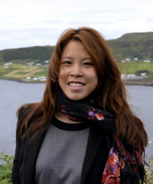 Clarissa Jeakings stands in front of a lake, smiling at the camera. She is wearing a grey shirt, a black blazer and a floral silk scarf.